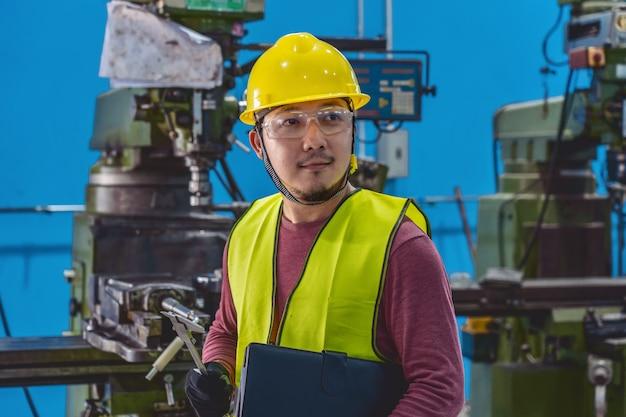 Asiatischer maschinist im sicherheitsanzug die jobliste mit spezifikationspapier überprüfend