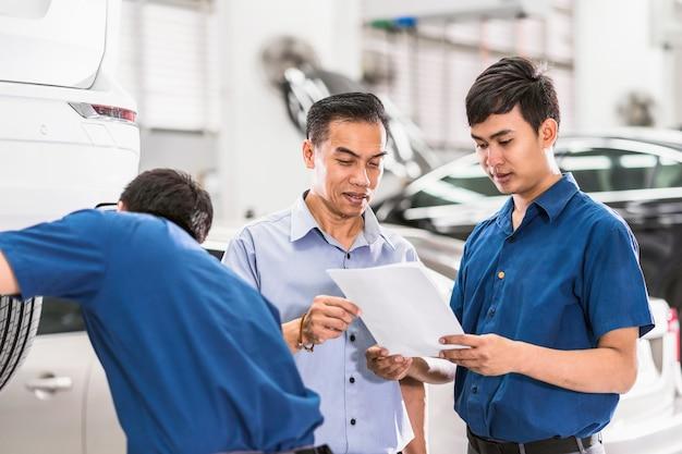 Asiatischer mechaniker, der dem kunden job über reparaturservice in der wartungsservice-mitte spricht und zeigt