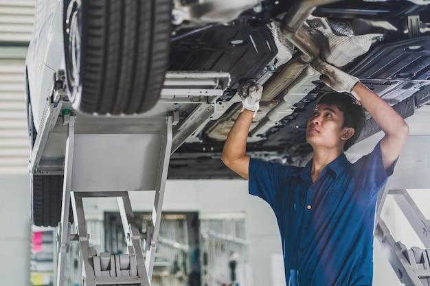 Asiatischer mechaniker, der im wartungsservice-center unter dem auto repariert und beleuchtet