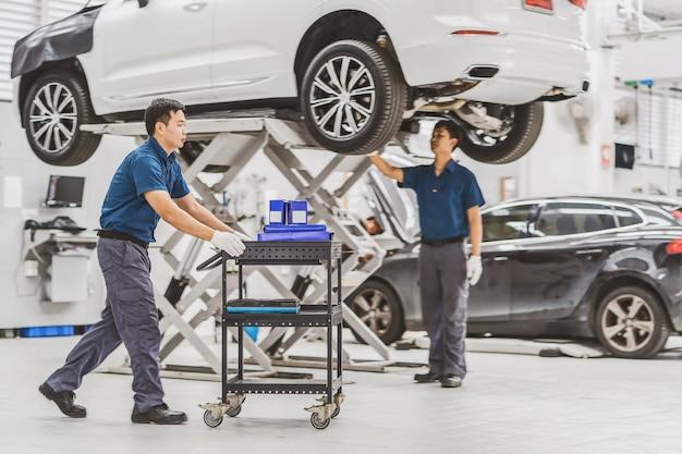 Asiatischer mechaniker push-warenkorb mit autoausrüstung über dem kollegen, der das auto überprüft und repariert