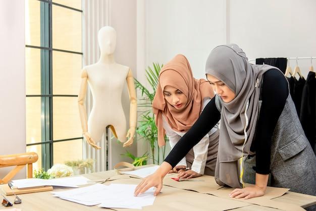 Asiatischer moslemischer frau fasion designer, der mit kollegen arbeitet