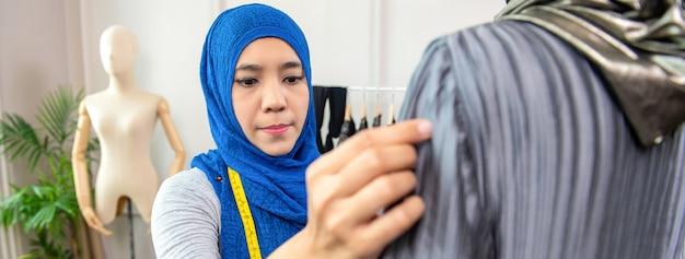Asiatischer moslemischer frauendesigner, der in ihrem schneidershop arbeitet