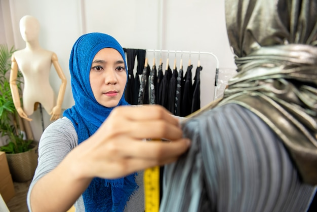 Asiatischer moslemischer frauendesigner, der in ihrer schneiderei arbeitet