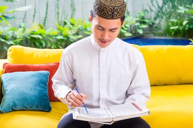 Asiatischer moslemischer mann, der koran oder quran liest