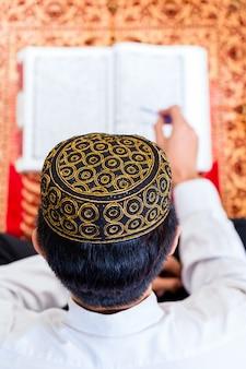 Asiatischer moslemischer mann, der koran oder quran studiert