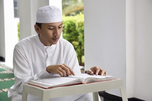 Asiatischer moslemischer mann der religion mit kappe heilige schrift koran lesend