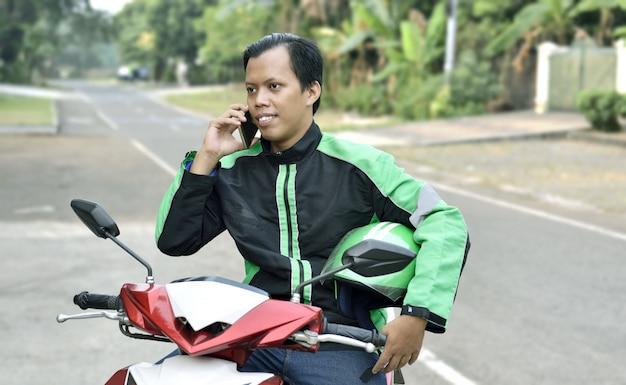 Asiatischer motorradtaximann, der das telefon verwendet