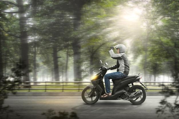Asiatischer motorradtaximann mit seinem motorrad