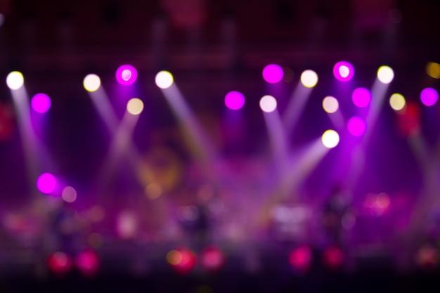 Asiatischer musiker, der die gitarre auf schwarzem hintergrund mit scheinwerferlicht spielt