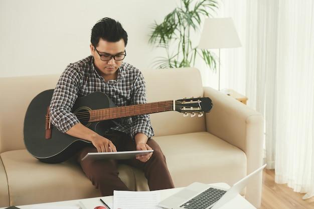Asiatischer musiker, der zu hause auf couch mit gitarre sitzt und tablette verwendet