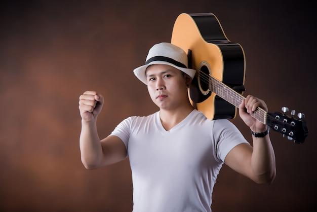 Asiatischer musiker des jungen mannes mit akustikgitarre