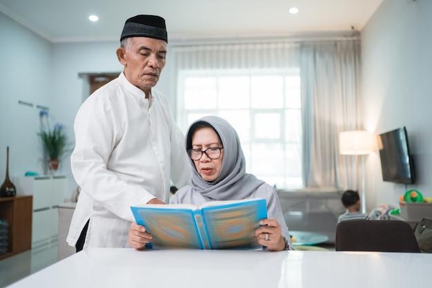 Asiatischer muslimischer älterer mann, der frau lehrt, koran oder koran im wohnzimmer zu lesen. muslimisches paar, das zu hause betet