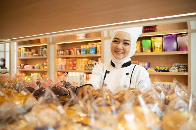 Asiatischer muslimischer bäcker, der an der kamera lächelt, die tablett in bäckerei hält, die sie besaß