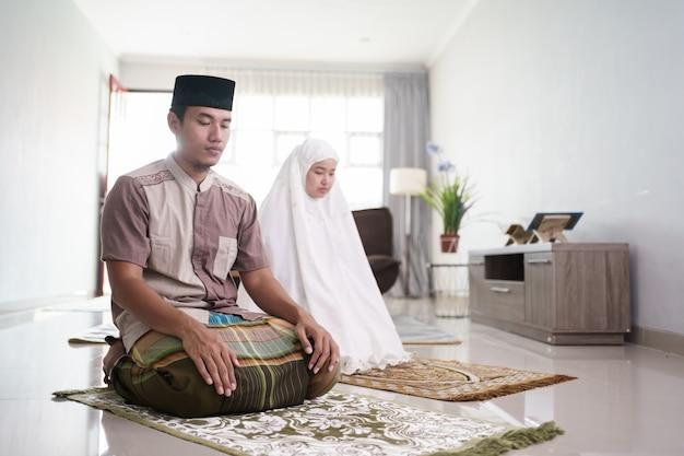 Asiatischer muslimischer ehemann und ehefrau, die jamaah zusammen zu hause beten