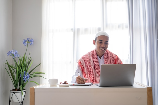 Asiatischer muslimischer geschäftsmann, der unter verwendung des laptops beim sitzen auf dem schreibtisch arbeitet