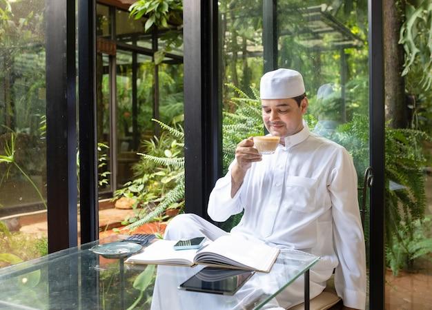 Asiatischer muslimischer geschäftsmann mittleren alters sitzen im kaffeegeschäft, trinken kaffee mit intelligentem handy auf tisch.