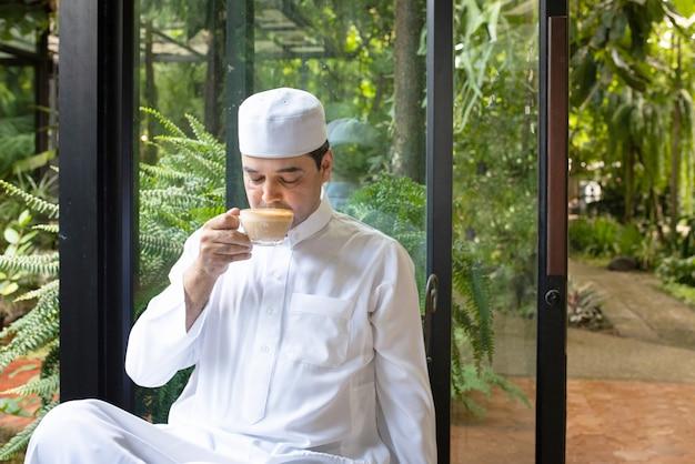 Asiatischer muslimischer geschäftsmann mittleren alters sitzen im kaffeegeschäft, trinken kaffee mit intelligentem handy