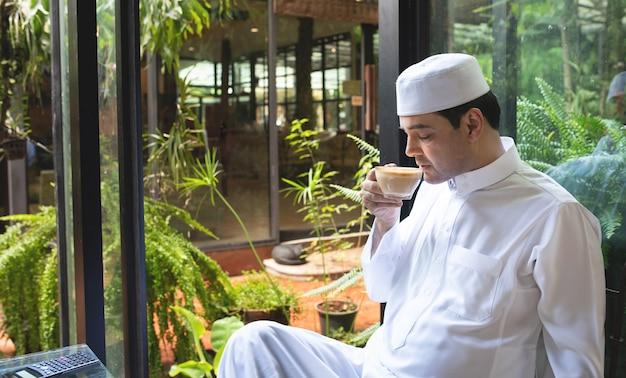 Asiatischer muslimischer geschäftsmann mittleren alters sitzen im kaffeegeschäft, trinken kaffee.