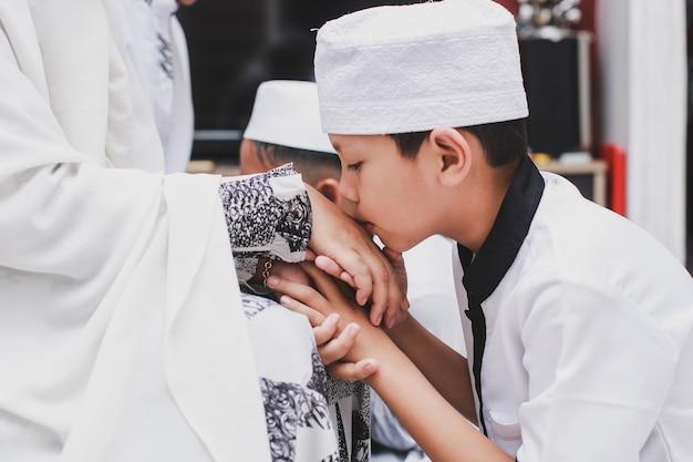 Asiatischer muslimischer junge mit traditionellem kleid, das zu hause bei der eid mubarak-feier die hand der mutter küsst