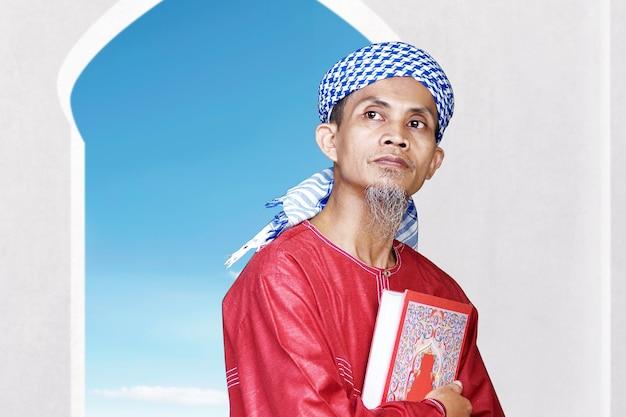 Asiatischer muslimischer mann, der den koran auf der moschee sitzt und hält