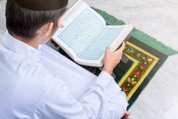 Asiatischer muslimischer mann, der den koran sitzt und liest