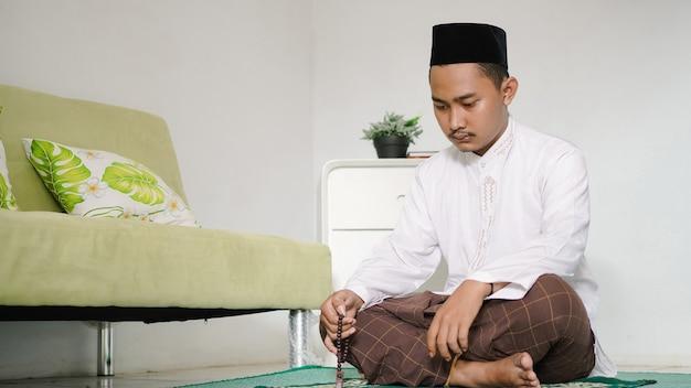 Asiatischer muslimischer mann, der dhikr tut
