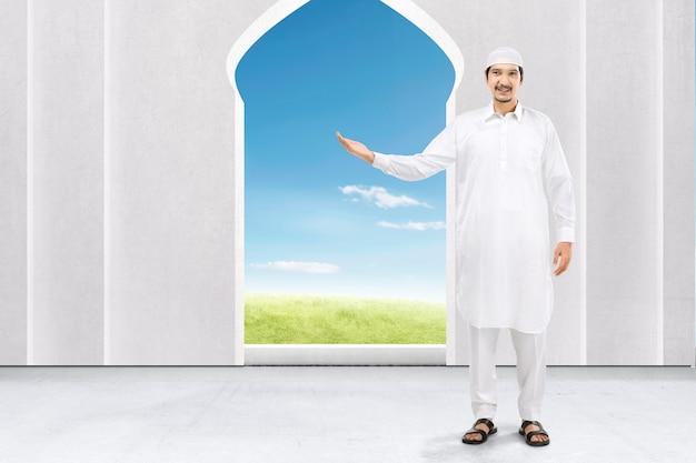 Asiatischer muslimischer mann, der etwas auf der moschee zeigt. leerer bereich für den kopierbereich