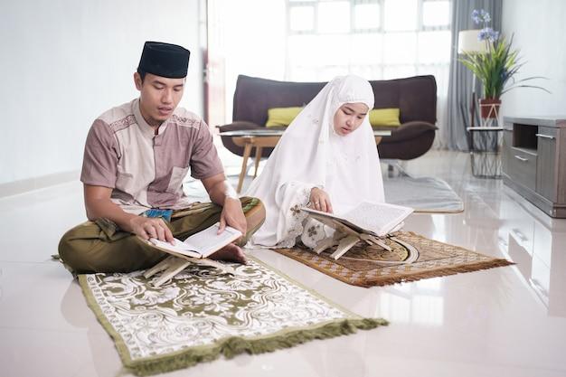 Asiatischer muslimischer mann, der frau unterrichtet, die koran oder koran im muslimischen wohnzimmerpaar liest, das zu hause betet