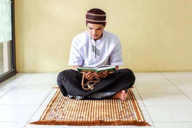 Asiatischer muslimischer mann, der gebetsperlen hält und das heilige buch alquran auf der gebetsmatte liest
