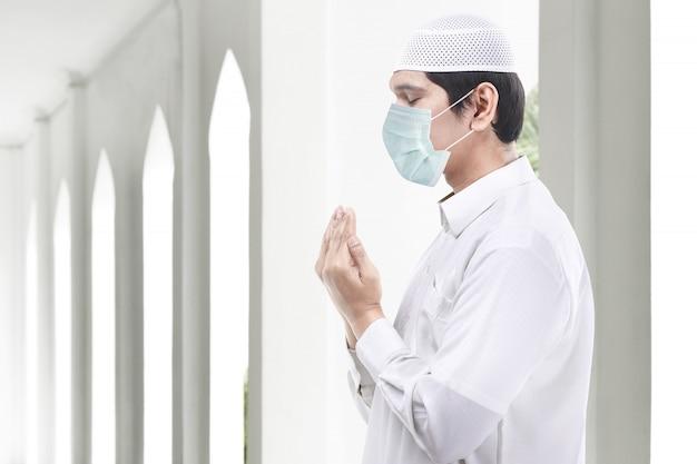 Asiatischer muslimischer mann, der grippemaske trägt, während erhobene hände stehen und beten