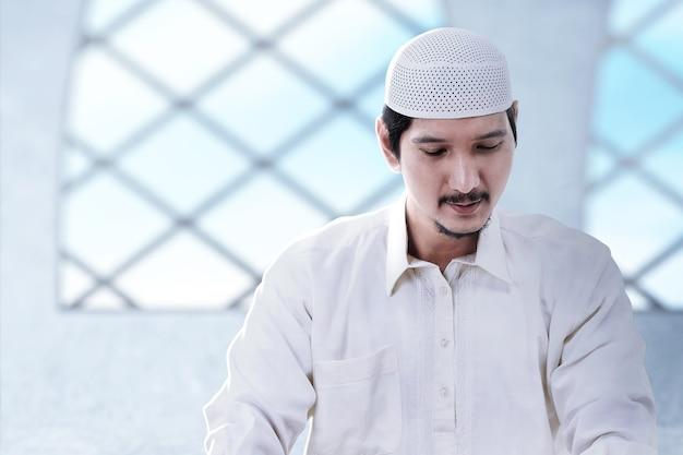 Asiatischer muslimischer mann, der in der moschee sitzt