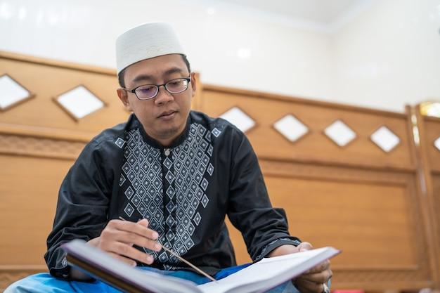 Asiatischer muslimischer mann, der koran liest