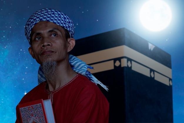 Asiatischer muslimischer mann, der koran mit kaaba-ansicht und nachtszenenhintergrund sitzt und hält