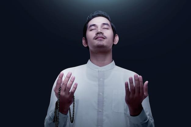 Asiatischer muslimischer mann, der mit gebetsperlen auf seinen händen betet