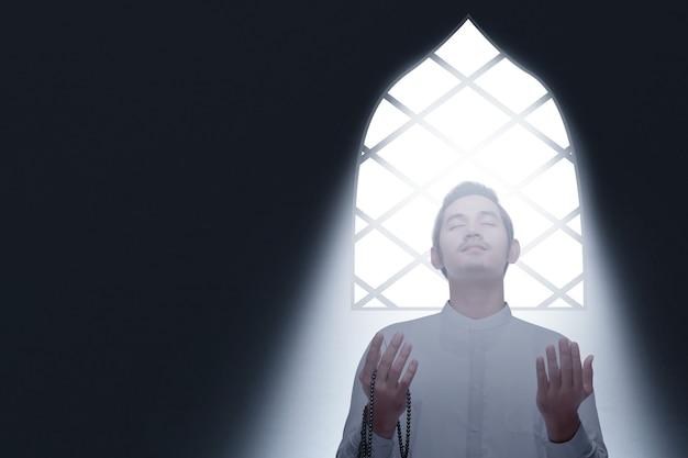 Asiatischer muslimischer mann, der mit gebetsperlen auf seinen händen innerhalb des raumes betet