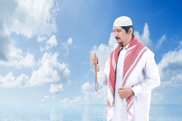 Asiatischer muslimischer mann, der mit gebetsperlen auf seinen händen mit einem blauen himmel betet