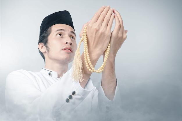 Asiatischer muslimischer mann, der mit gebetsperlen auf seinen händen mit nebelhintergrund betet