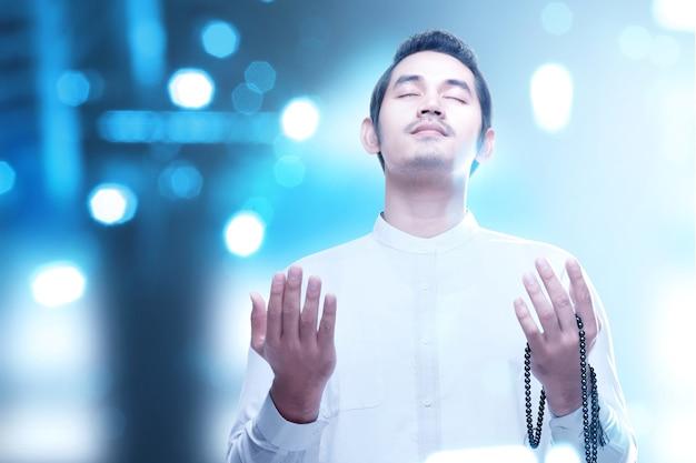 Asiatischer muslimischer mann, der mit gebetsperlen auf seinen händen mit verschwommenem licht betet