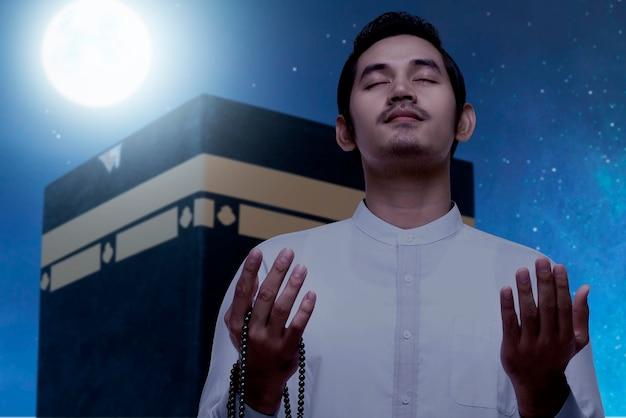 Asiatischer muslimischer mann, der mit gebetsperlen mit kaaba-ansicht und nachtszenenhintergrund steht und betet