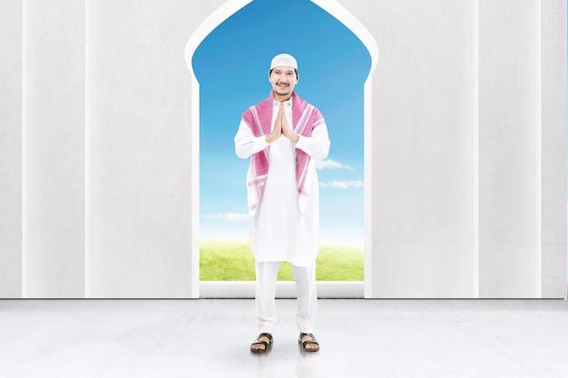 Asiatischer muslimischer mann, der mit grußgeste auf der moschee steht