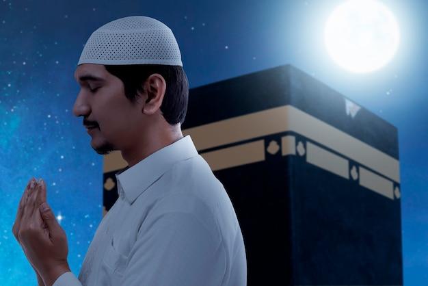 Asiatischer muslimischer mann, der mit kaaba-ansicht und nachtszenenhintergrund steht und betet