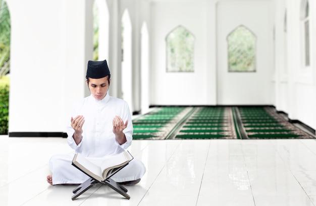 Asiatischer muslimischer mann, der sitzt, während erhobene hände und auf der moschee beten