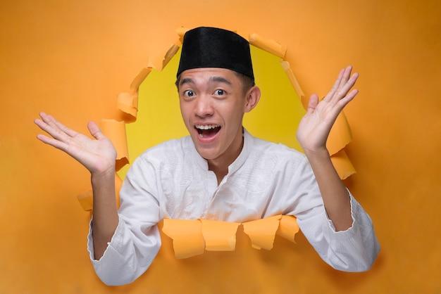 Asiatischer muslimischer mann feiern gestenposen durch zerrissenes gelbes papierloch, tragen muslimisches tuch mit schädelkappe und begrüßen ramadan oder eid al-fitr.