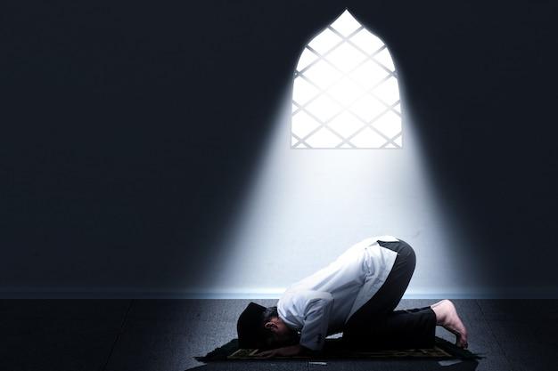 Asiatischer muslimischer mann in der gebetsstellung (salat) auf dem gebetsteppich innerhalb des raumes