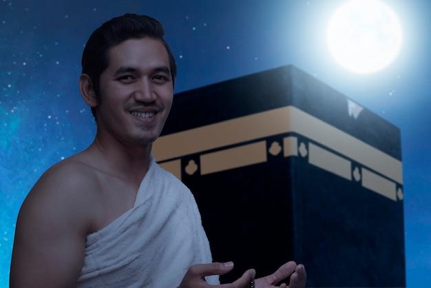 Asiatischer muslimischer mann in ihram-kleidung, der mit gebetsperlen mit kaaba- und nachtszenenhintergrund steht und betet