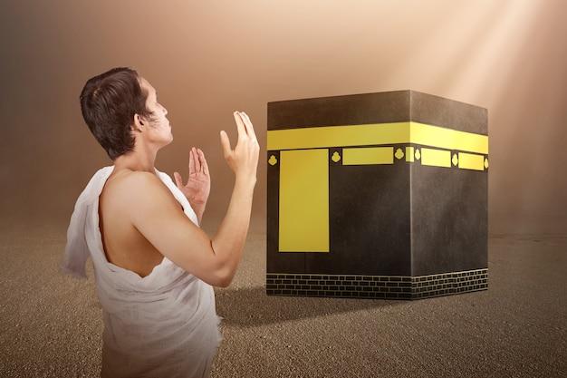 Asiatischer muslimischer mann in ihram-kleidung, der vor der kaaba mit sonnenlichthintergrund steht und betet