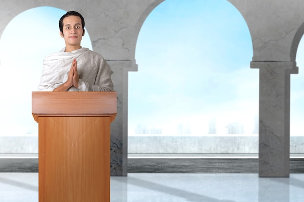 Asiatischer muslimischer mann in ihreram kleidung, die mit grußgeste auf der moschee steht