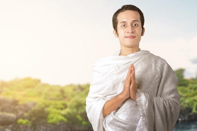 Asiatischer muslimischer mann in ihreram kleidung, die mit grußgeste mit einem blauen himmelhintergrund steht