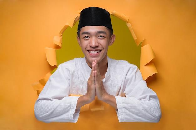 Asiatischer muslimischer mann lächelt und zeigt grußgeste posiert durch zerrissenes gelbes papierloch, muslimisches tuch mit schädelkappe tragend, begrüßungsgeste zur feier des ramadan oder von eid al-fitr.