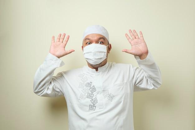 Asiatischer muslimischer mann mit maske, der glücklich freudig tanzt und gute nachrichten feiert